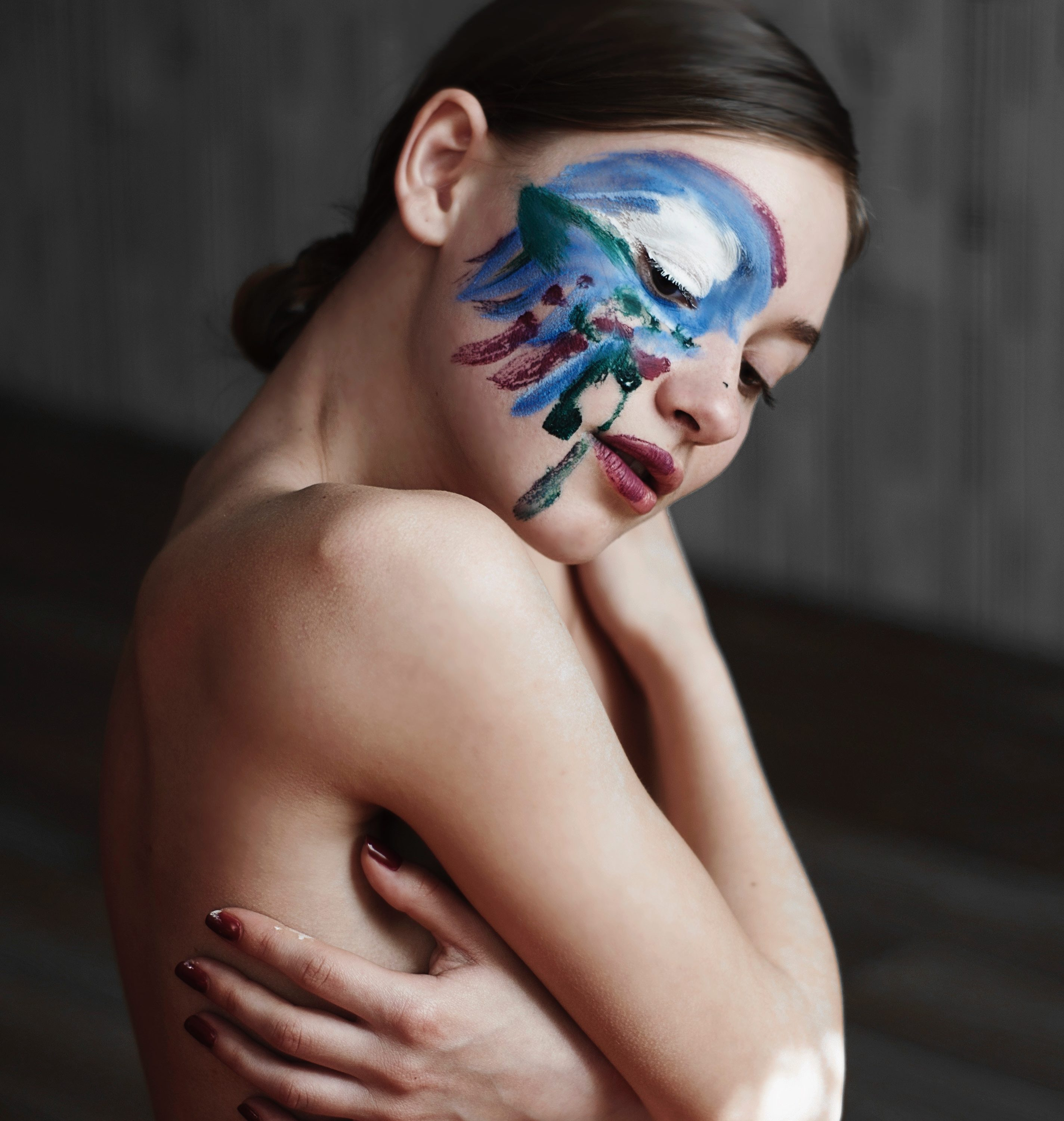 Model with paint on her face to symbolise creative side hustles